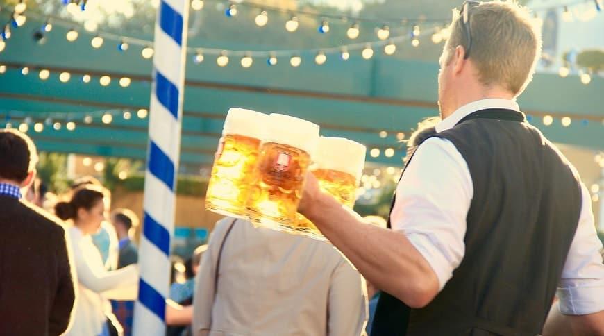 מלצר מגיש בבר פתוח 3 כוסות בירה